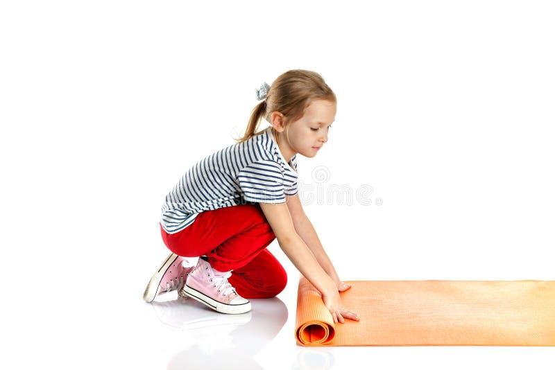 Маленькая девочка делая гимнастические тренировки на циновке йоги делать fitne стоковая фотография