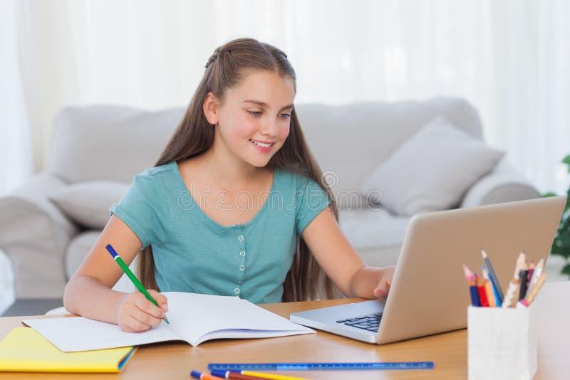 Маленькая девочка делая ее домашнюю работу дома стоковая фотография rf