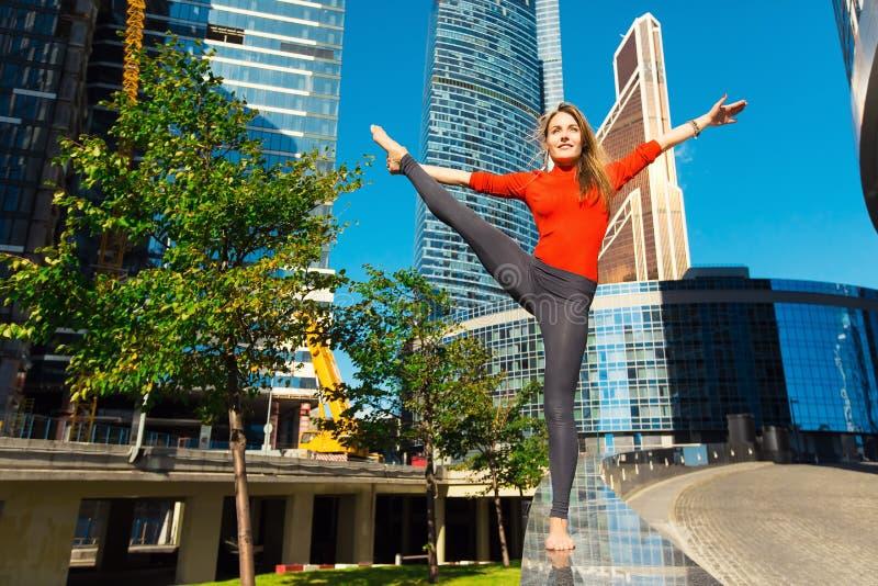 Маленькая девочка делая йогу outdoors в городе стоковые изображения
