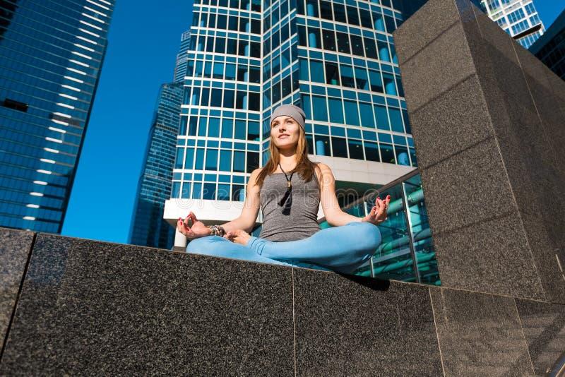 Маленькая девочка делая йогу outdoors в городе стоковое изображение rf