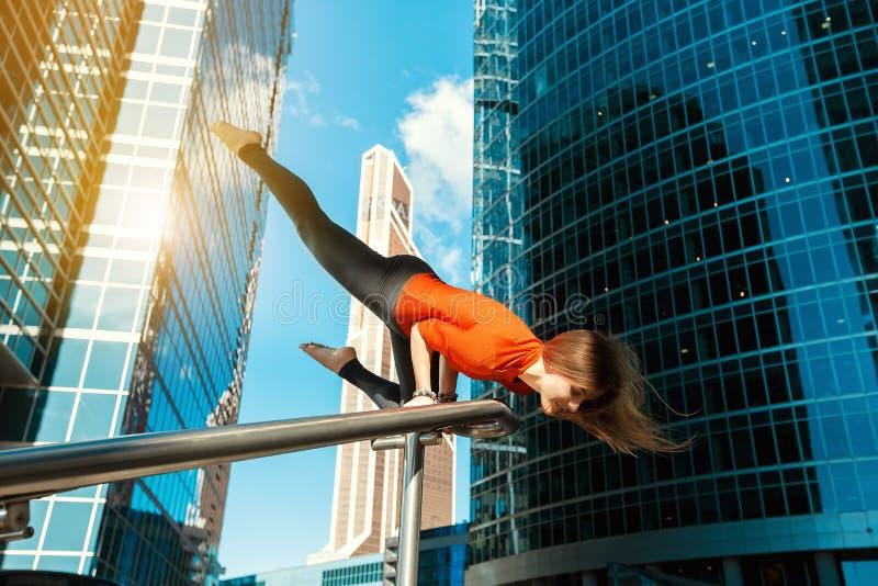 Маленькая девочка делая йогу outdoors в городе стоковая фотография