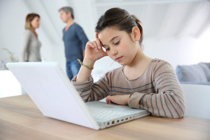 Маленькая девочка делая домашнюю работу на компьтер-книжке стоковое изображение