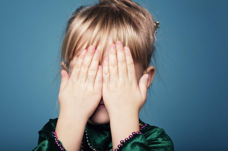 Маленькая девочка играет прятк стоковые фотографии rf