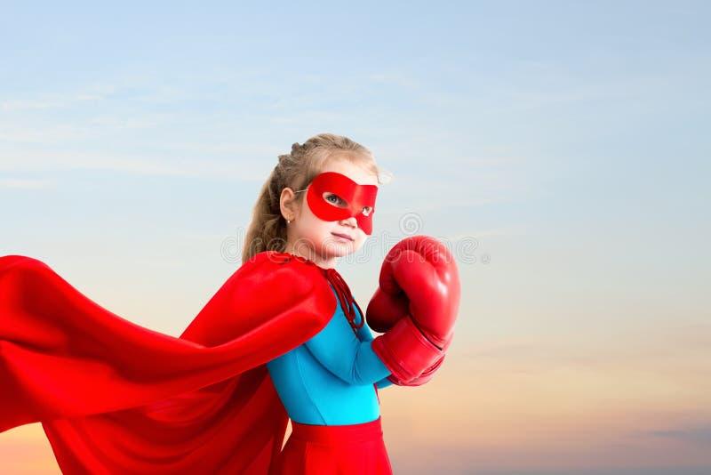 Маленькая девочка играет супергероя на предпосылке неба захода солнца стоковое изображение rf
