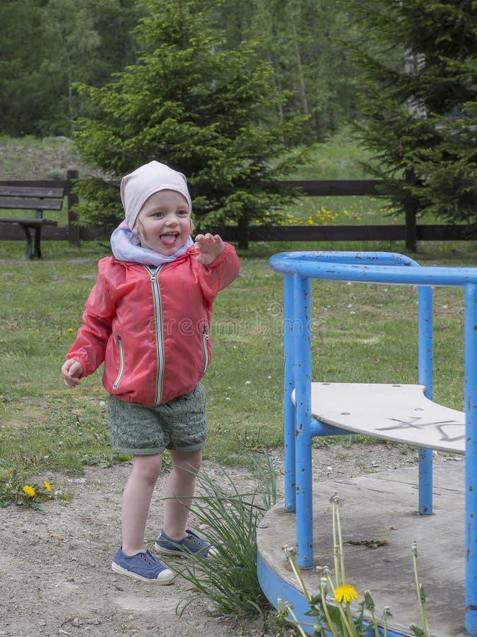 Маленькая девочка играет счастливое на спортивной площадке горы стоковое изображение rf
