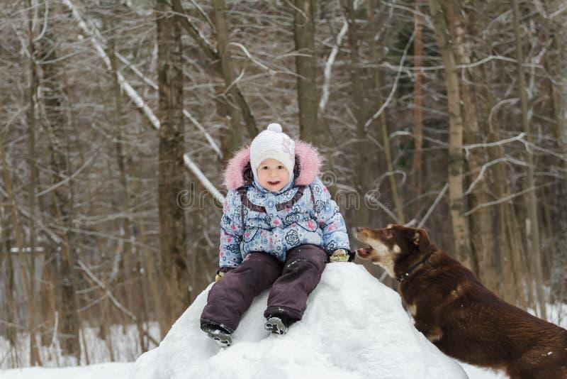 Маленькая девочка играя в лесе зимы на снежном холме стоковые фотографии rf