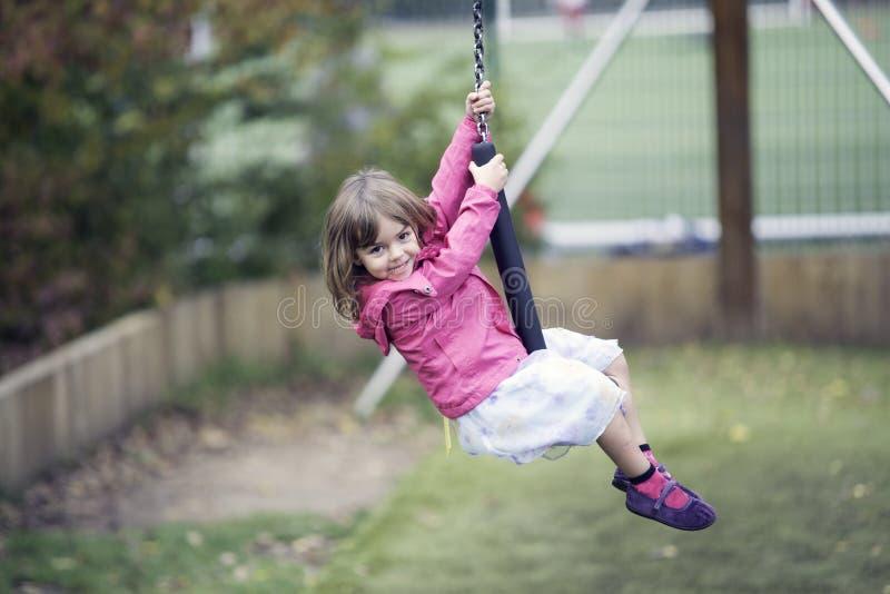 Маленькая девочка играя в застежка-молнии стоковое изображение