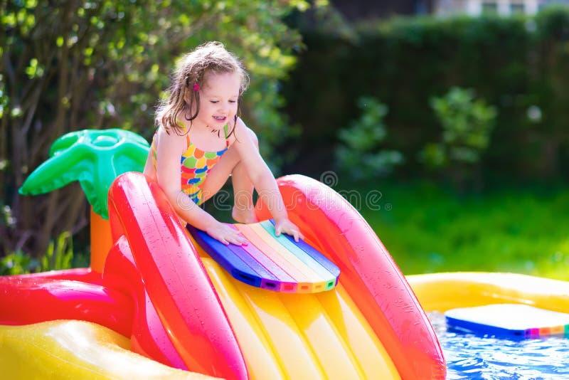 Маленькая девочка играя в раздувном бассейне сада стоковое изображение rf
