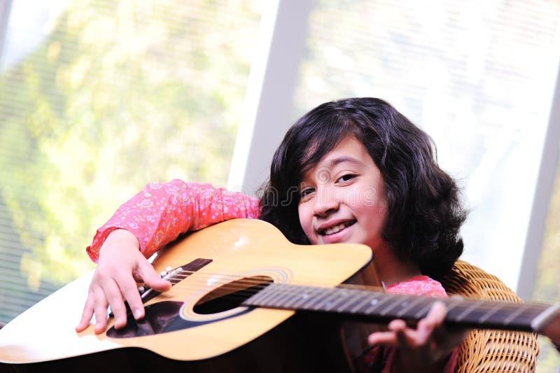 Маленькая девочка играя гитару стоковая фотография rf
