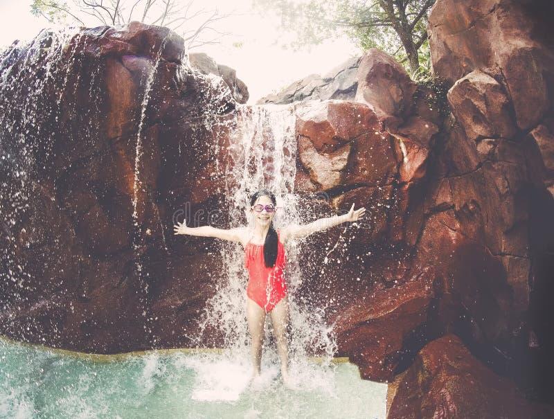 Маленькая девочка играя и брызгая в водопаде стоковые фото