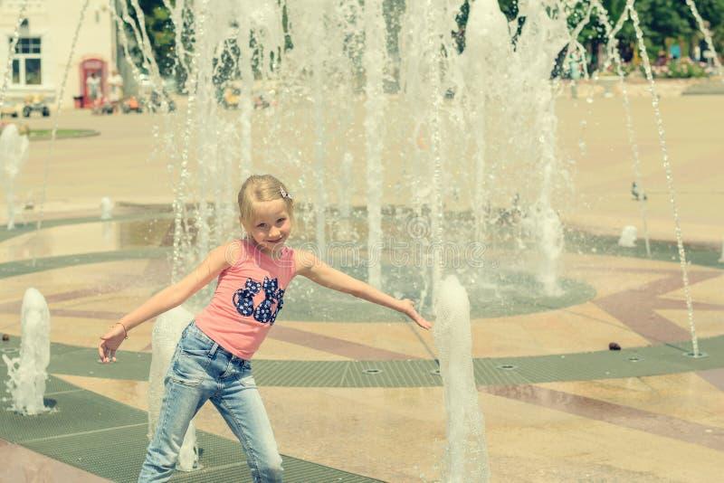 Маленькая девочка играя с водой в фонтане города стоковые фотографии rf