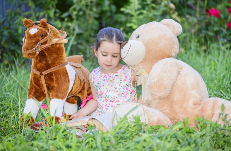 Маленькая девочка играя с игрушками на зеленой траве снаружи в задворк стоковое изображение