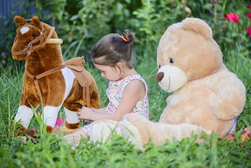 Маленькая девочка играя с игрушками на зеленой траве снаружи в задворк стоковое изображение rf