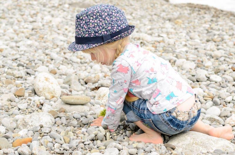 Маленькая девочка играя с камнями на пляже стоковые изображения rf