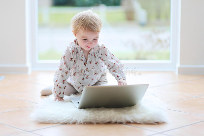 Маленькая девочка играя с компьтер-книжкой на поле стоковое фото