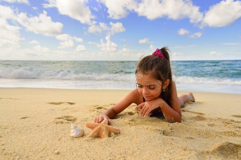 Маленькая девочка играя с морской звёздой на пляже стоковые изображения rf