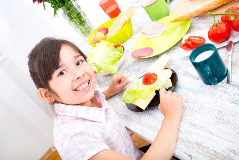 Маленькая девочка имея завтрак дома стоковые фото