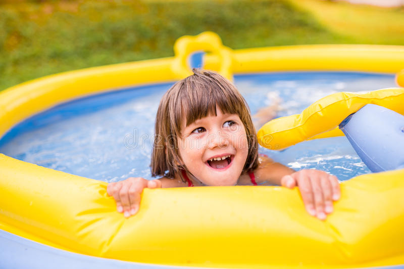 Маленькая девочка имея потеху в бассейне сада стоковые фото