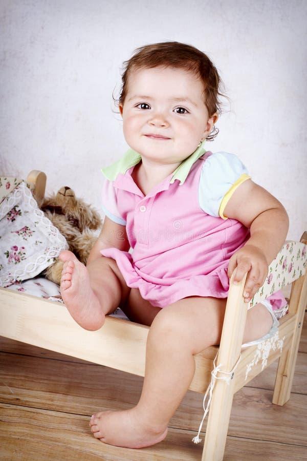 Маленькая девочка имея потеху в малой кровати стоковые изображения