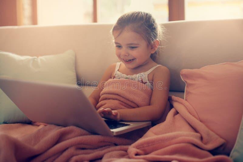 Маленькая девочка используя ее компьтер-книжку стоковые фотографии rf