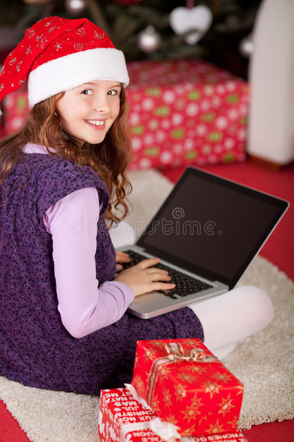 Маленькая девочка используя компьтер-книжку между подарками рождества стоковое фото rf