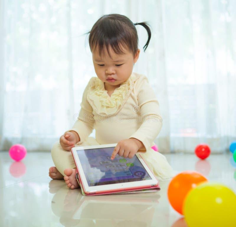 Маленькая девочка используя таблетку стоковые фото