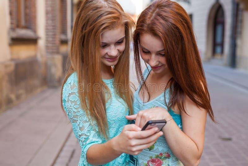 Маленькая девочка 2 используя GPS в мобильном телефоне Городское backbround стоковое фото
