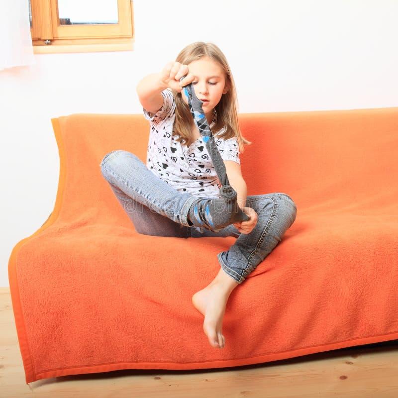 Маленькая девочка лишая носки стоковое фото rf