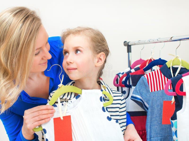 Маленькая девочка и ее мама выбирая платье стоковое фото