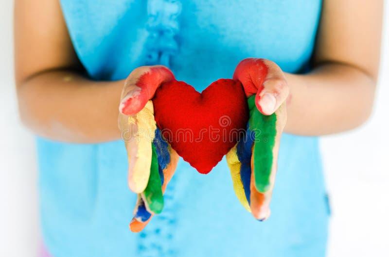 Маленькая девочка и красное сердце в наличии стоковая фотография rf