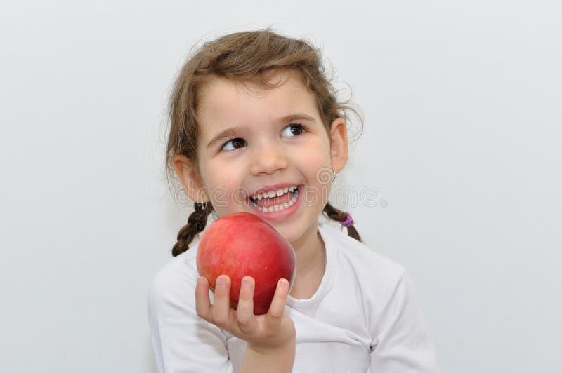Маленькая девочка и красное яблоко стоковая фотография rf