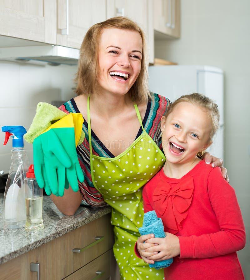 Маленькая девочка и мама аккуратные вверх на кухне стоковые изображения rf