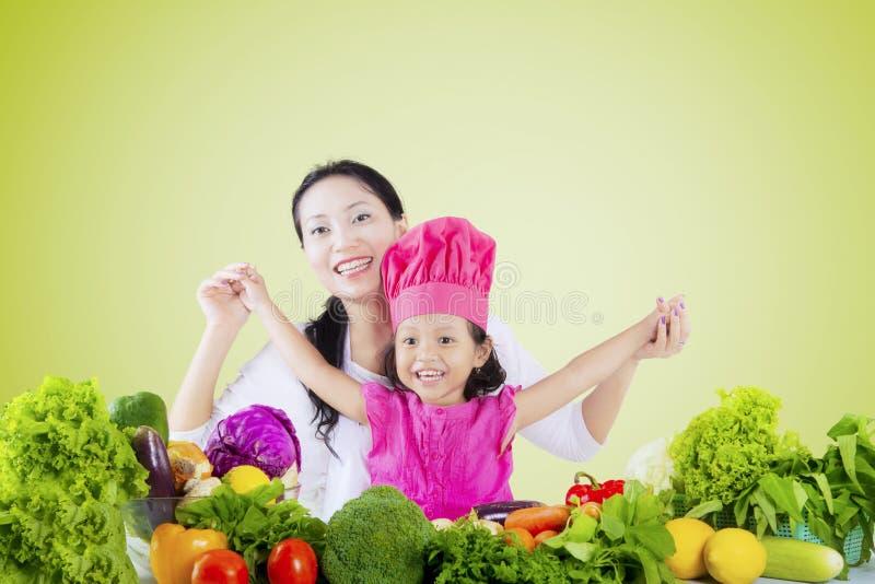 Маленькая девочка и мать с овощем стоковое фото rf