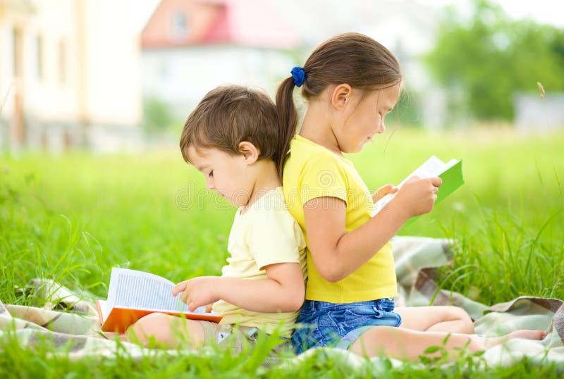 Маленькая девочка и мальчик книга чтения outdoors стоковые изображения