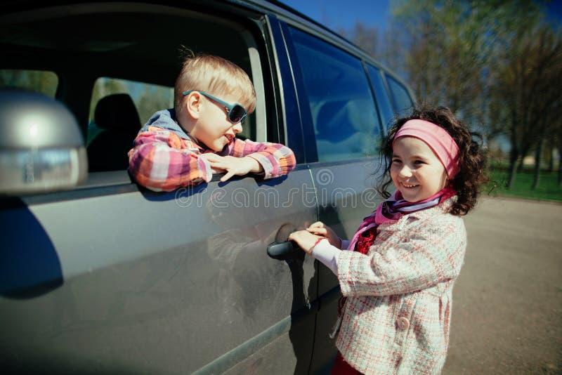 Маленькая девочка и мальчик управляя автомобилем стоковое изображение