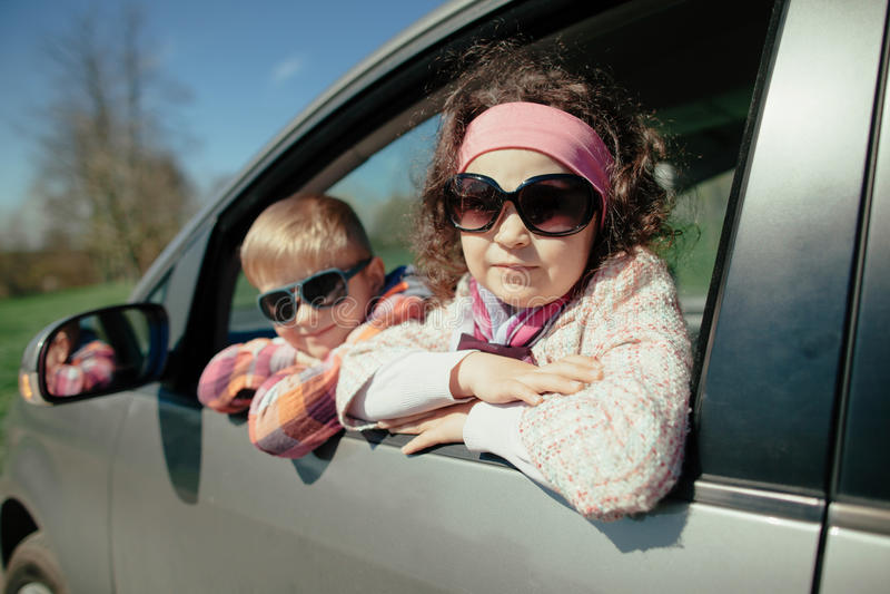 Маленькая девочка и мальчик управляя автомобилем стоковая фотография