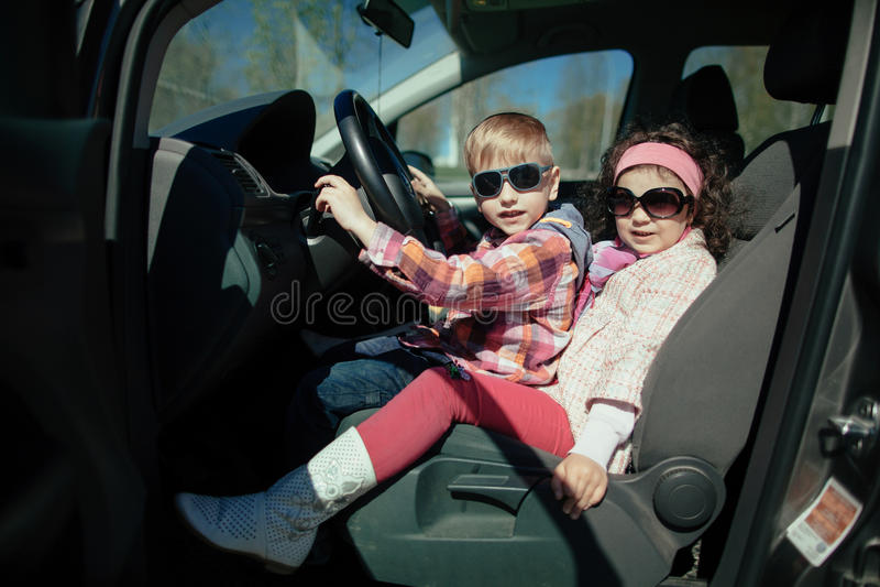 Маленькая девочка и мальчик управляя автомобилем стоковое фото