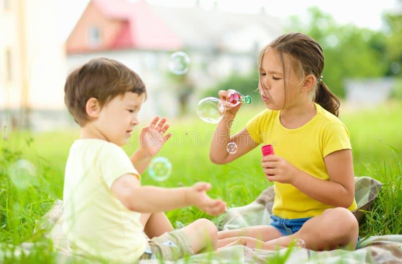 Маленькая девочка и мальчик дуют пузыри мыла стоковое фото rf