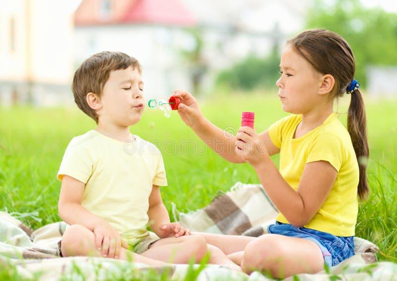 Маленькая девочка и мальчик дуют пузыри мыла стоковые изображения rf
