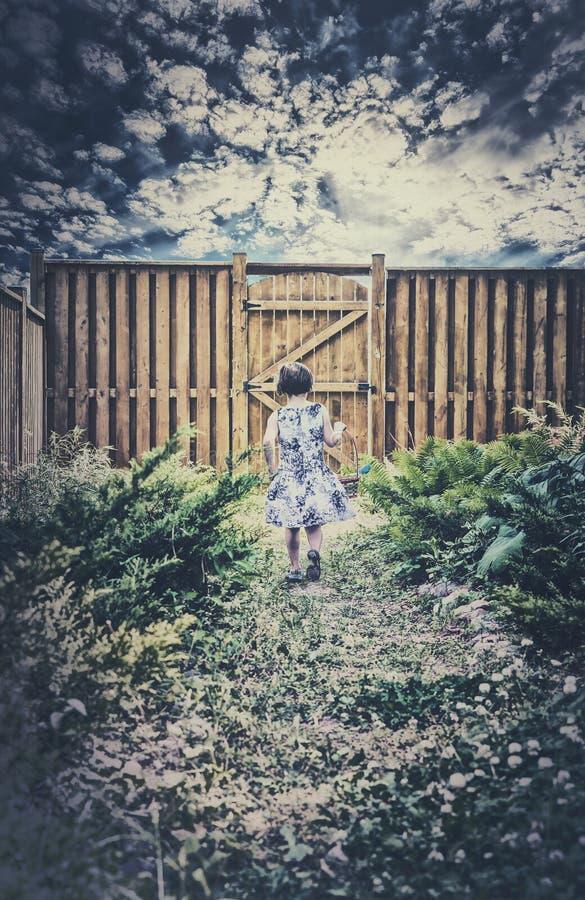 Маленькая девочка идя вниз с пути держа корзину пасхи стоковое фото