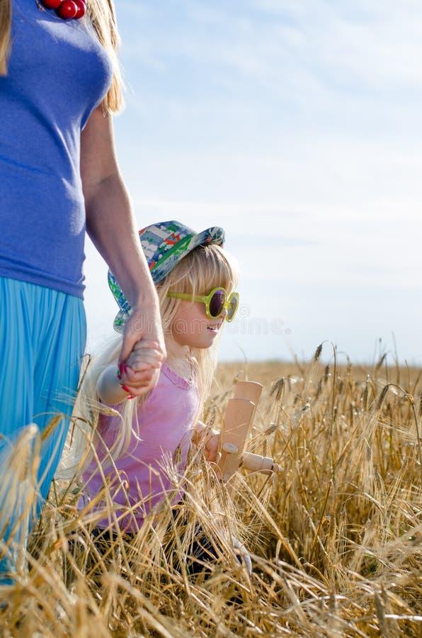 Маленькая девочка идя в пшеничное поле с матерью стоковые фотографии rf