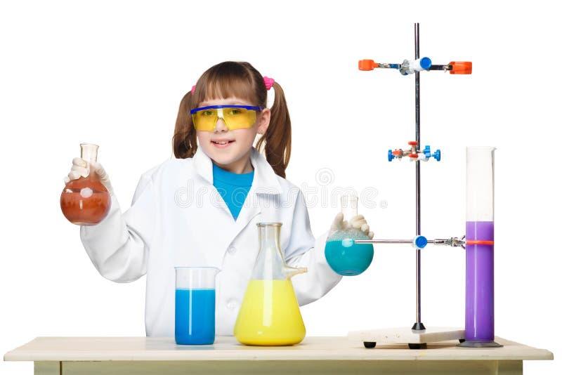 Маленькая девочка как химик делая эксперимент с стоковые изображения