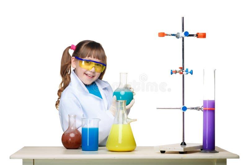 Маленькая девочка как химик делая эксперимент с стоковые фотографии rf