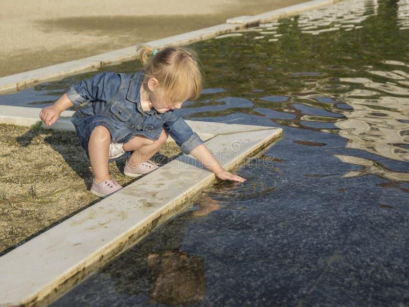 Маленькая девочка касается воде пруда стоковые фотографии rf
