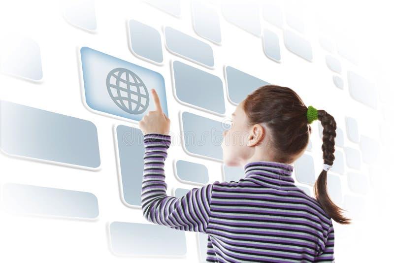Маленькая девочка касаясь кнопке виртуального экрана с изображением глобуса стоковое изображение