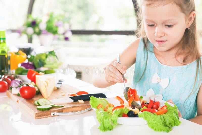 Маленькая девочка крупного плана милая делая салат Варить ребенка еда здоровая стоковое фото rf