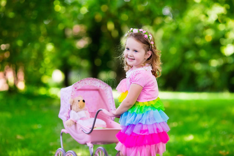 Маленькая девочка нажимая прогулочную коляску игрушки с куклой стоковая фотография
