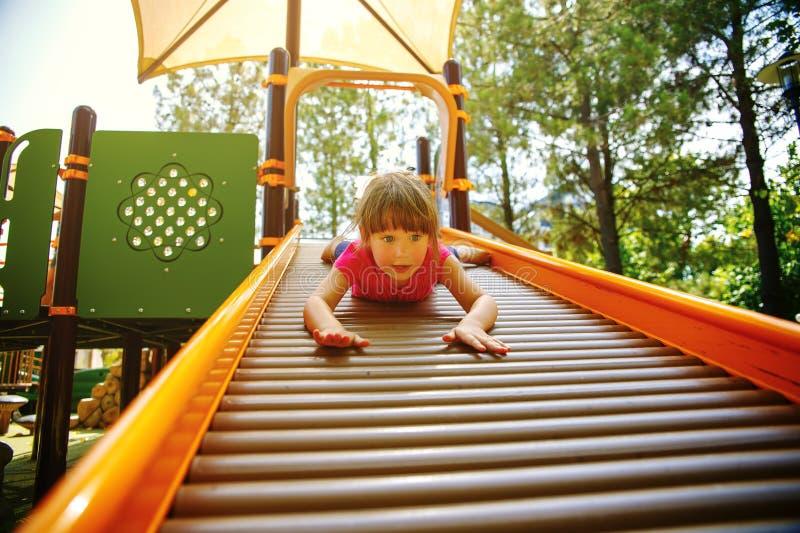 Маленькая девочка наслаждается спортивной площадкой стоковое фото rf