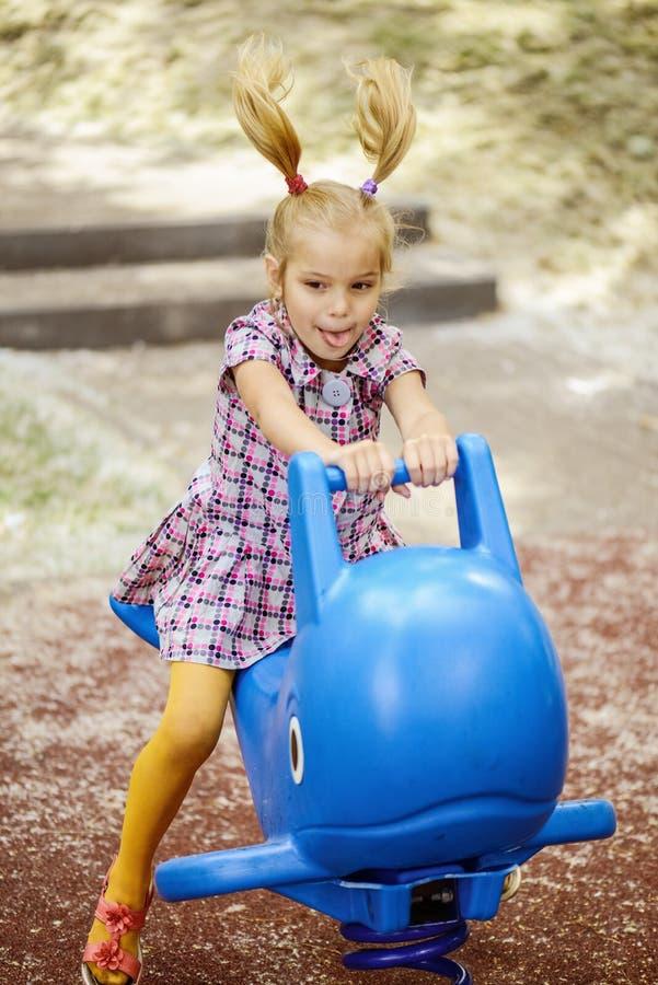 Маленькая девочка на качании в парке города детей стоковое изображение