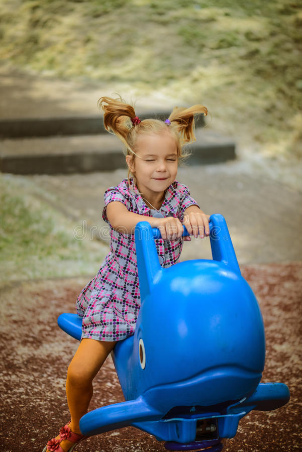 Маленькая девочка на качании в парке города детей стоковая фотография